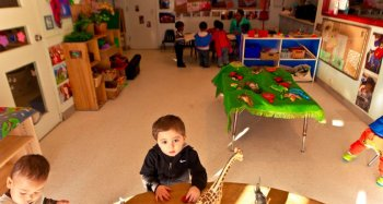 Child studies practicum in daycare with boy playing with car on a table with animals, close-up