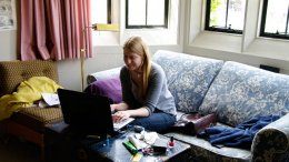 Female student sitting on a couch typing on a laptop.